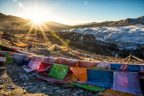Assorted-color Flags on Mountain during Sunrise
