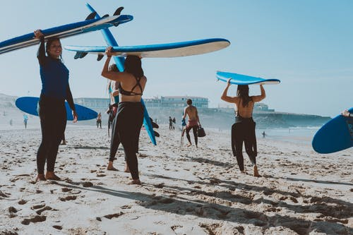 Photo of People Carrying Surfboards