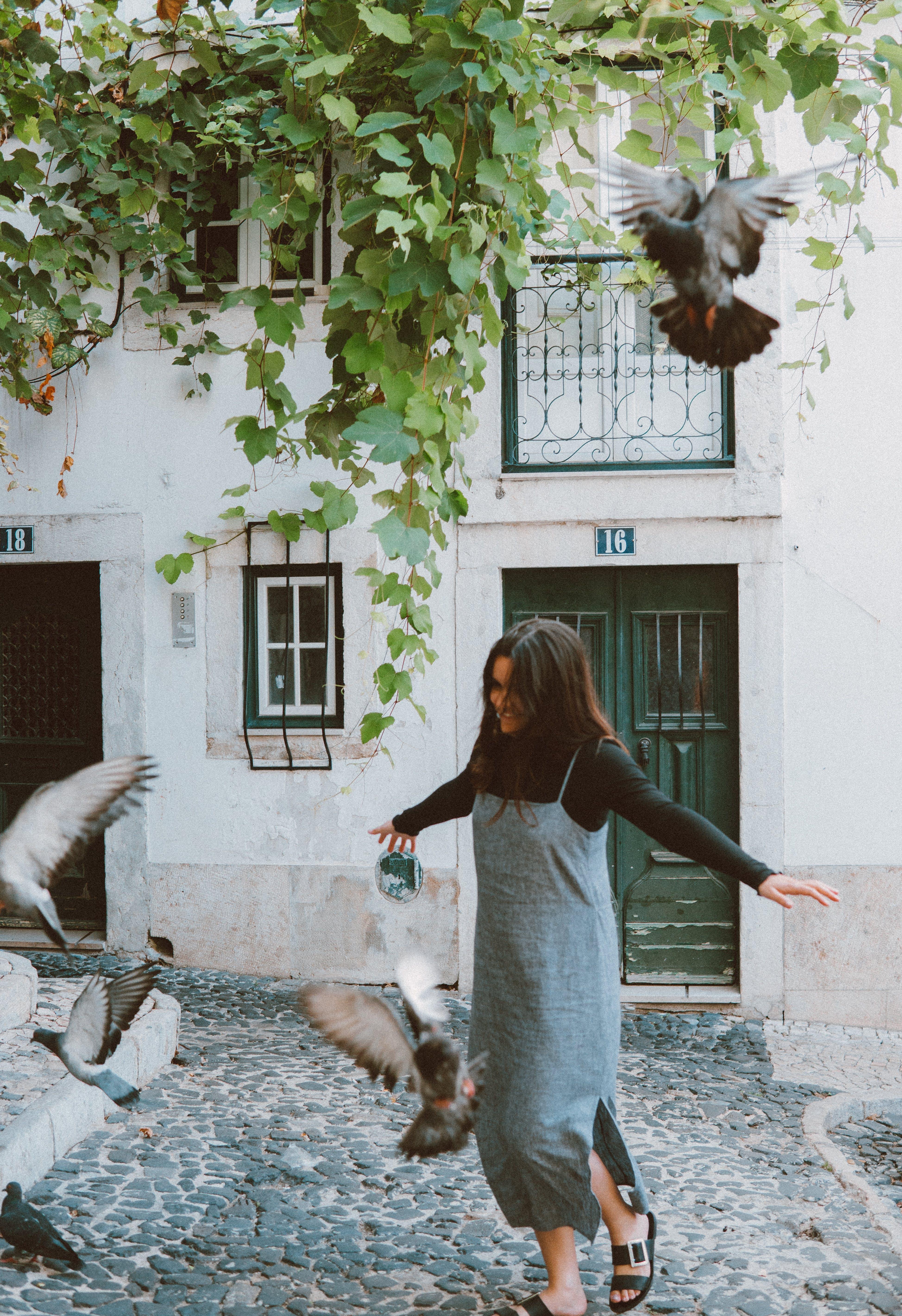 Woman Chasing Flock of Pigeons