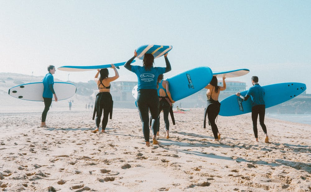 Group of people carrying surfboards.   Photo: Pexels
