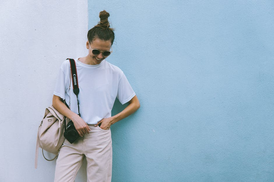 Woman wearing white crew neck t shirt with black canon dslr on her shoulder