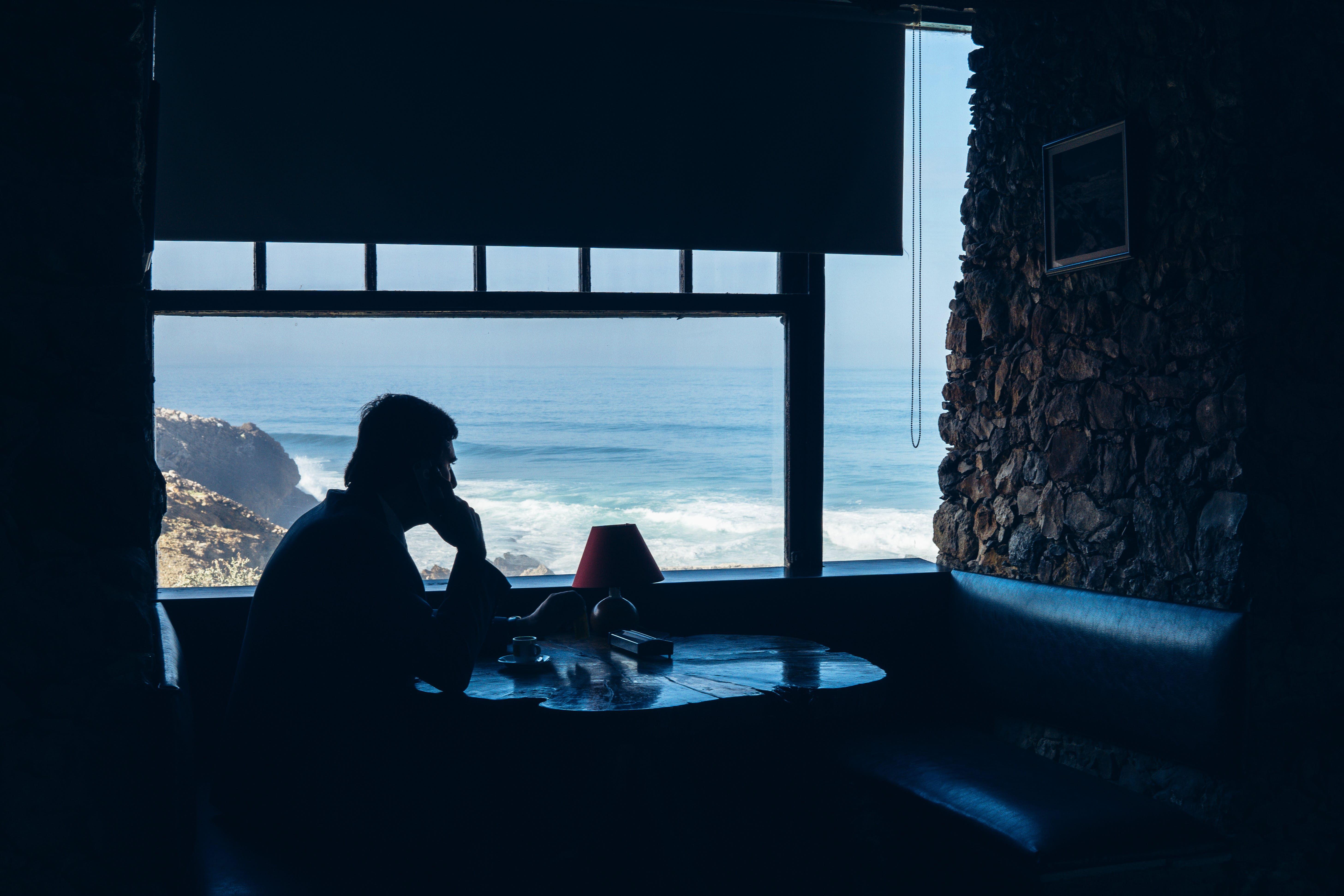 Silhouette of Man Sitting in Front of Table Beside Window