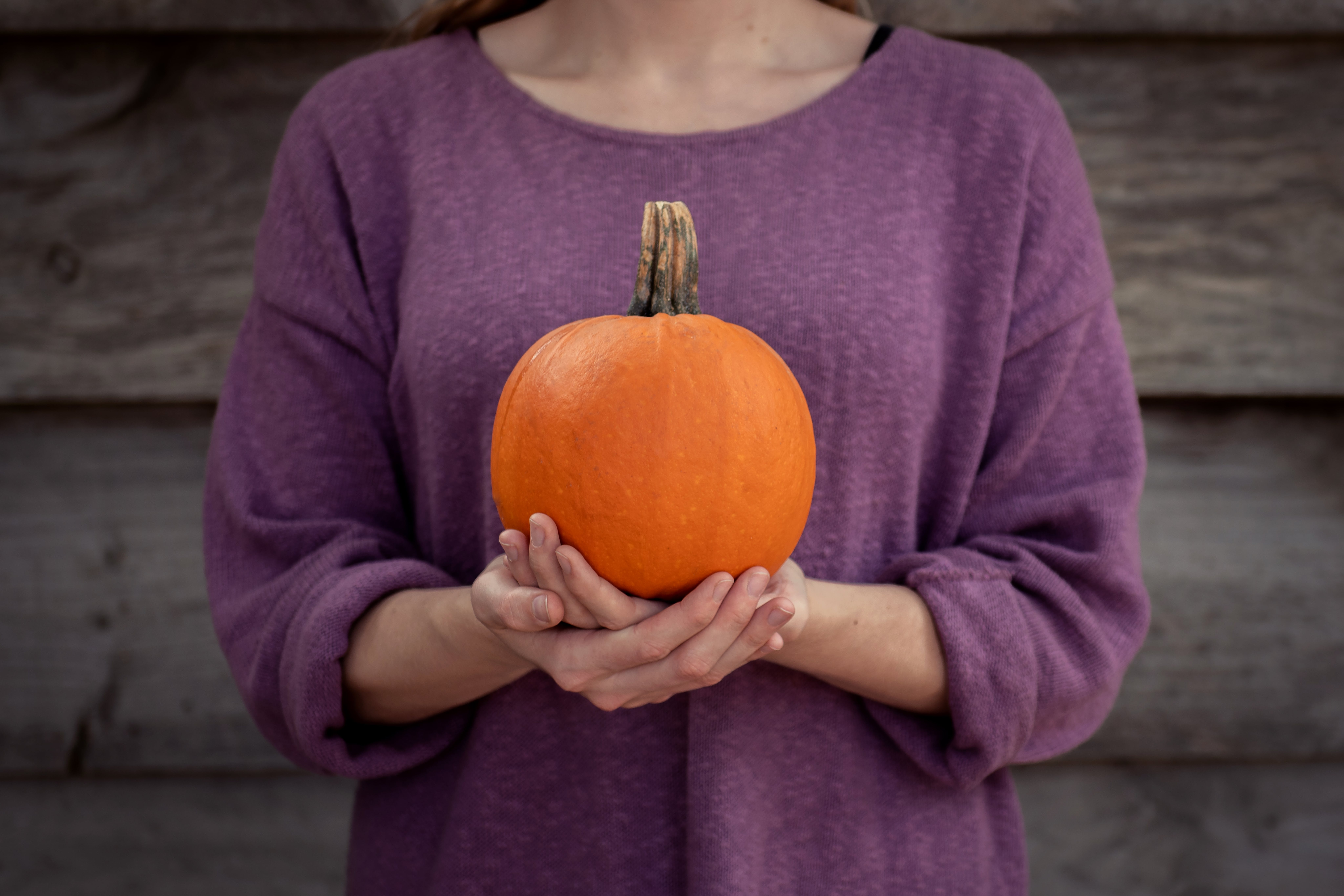 Photo of Woman Carrying Pumpkin on Both Hands