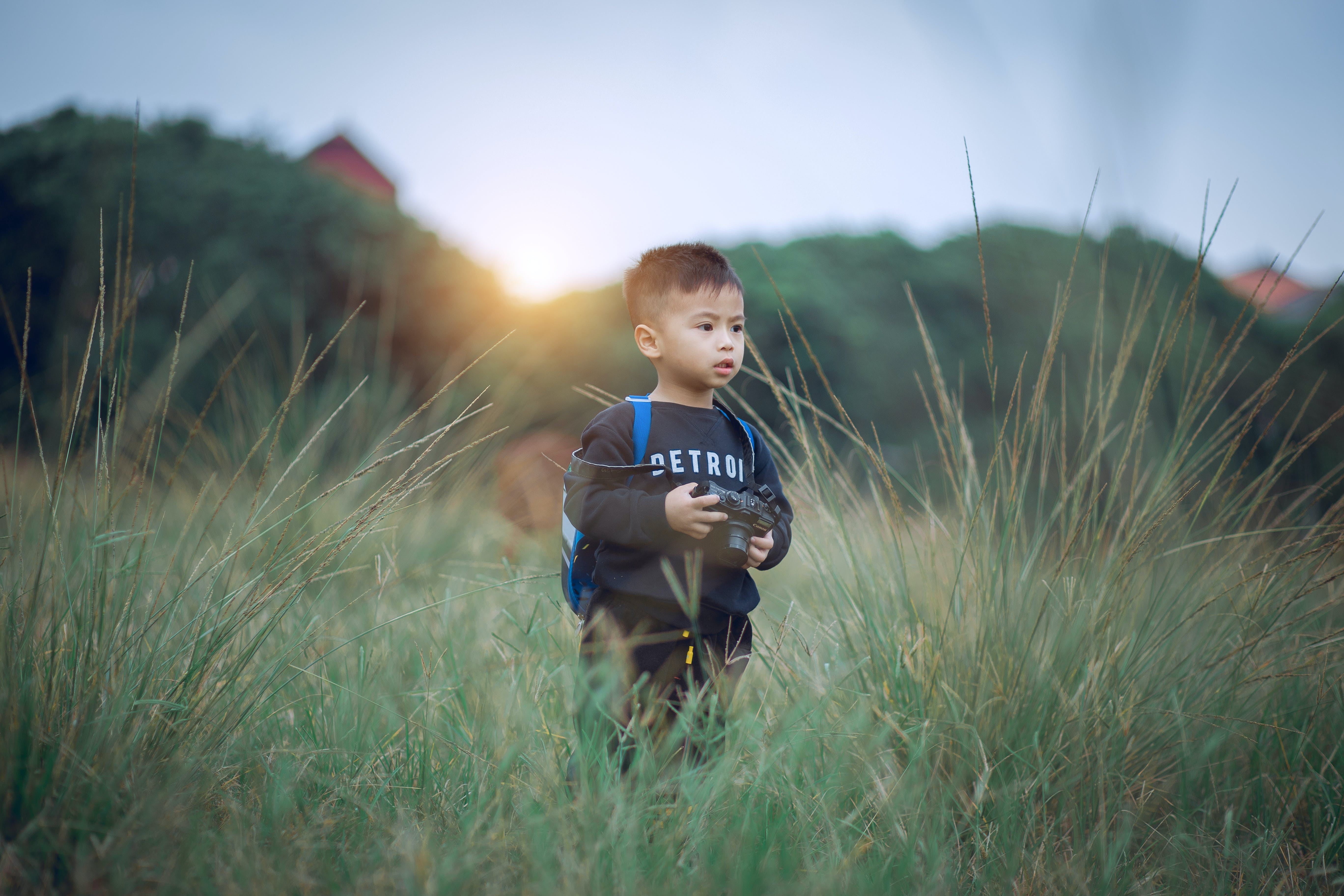 Shallow Focus Photography of Boy Standing on Green Grass Holding Camera