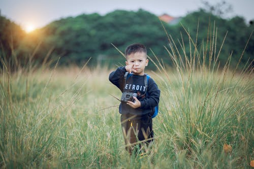 Boy Standing on Green Field Holding Black Camera