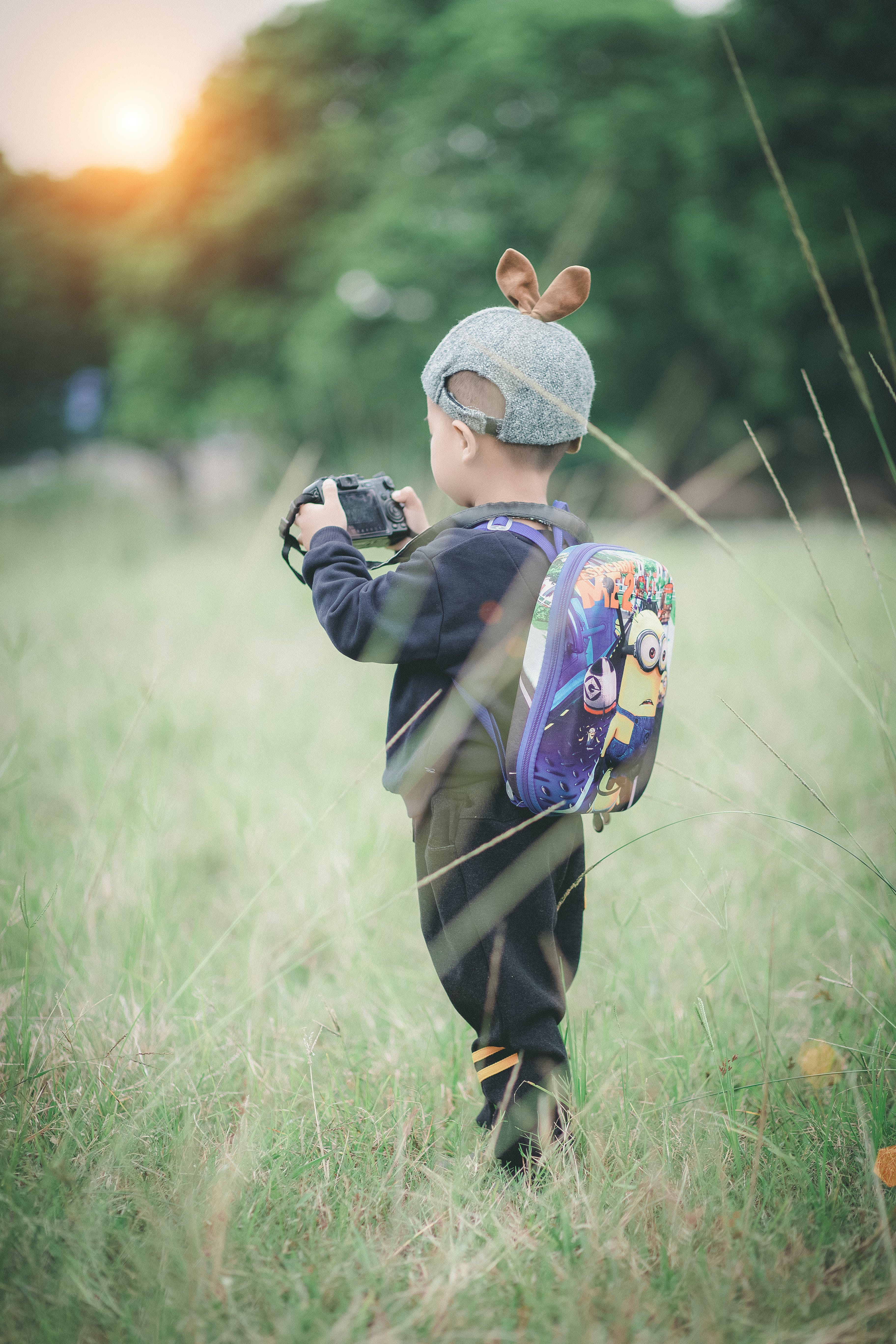 Boy Carrying Backpack Holding Camera Standing on Green Grass