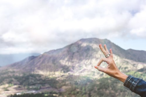 Persona Che Mostra Segno Ok Mano Che Si Affaccia Sulla Montagna
