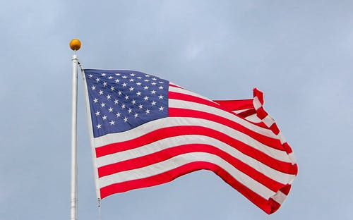 Usa Flag Waving On White Metal Pole