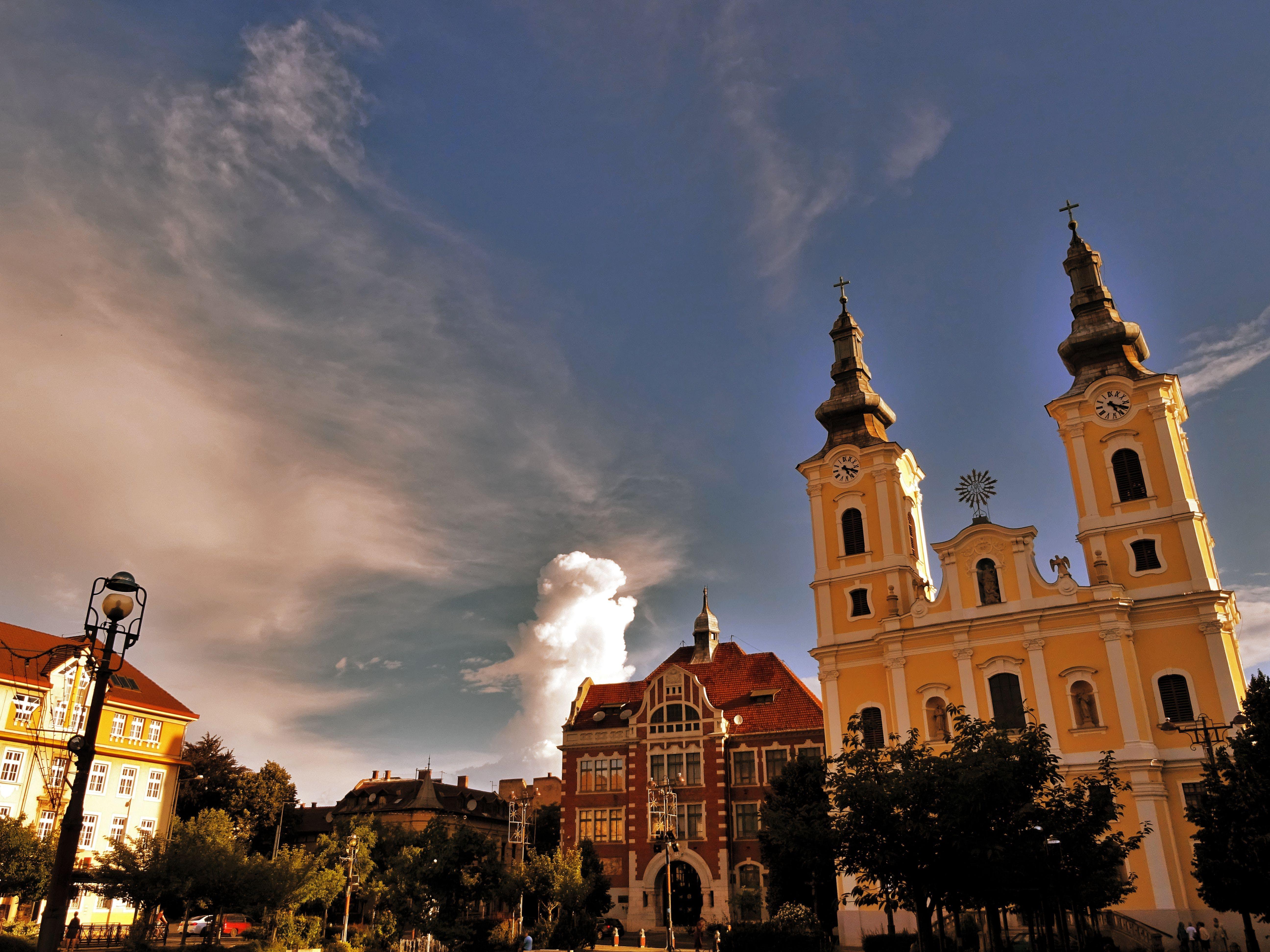 Cathedral Beside Building Under Blue Sky