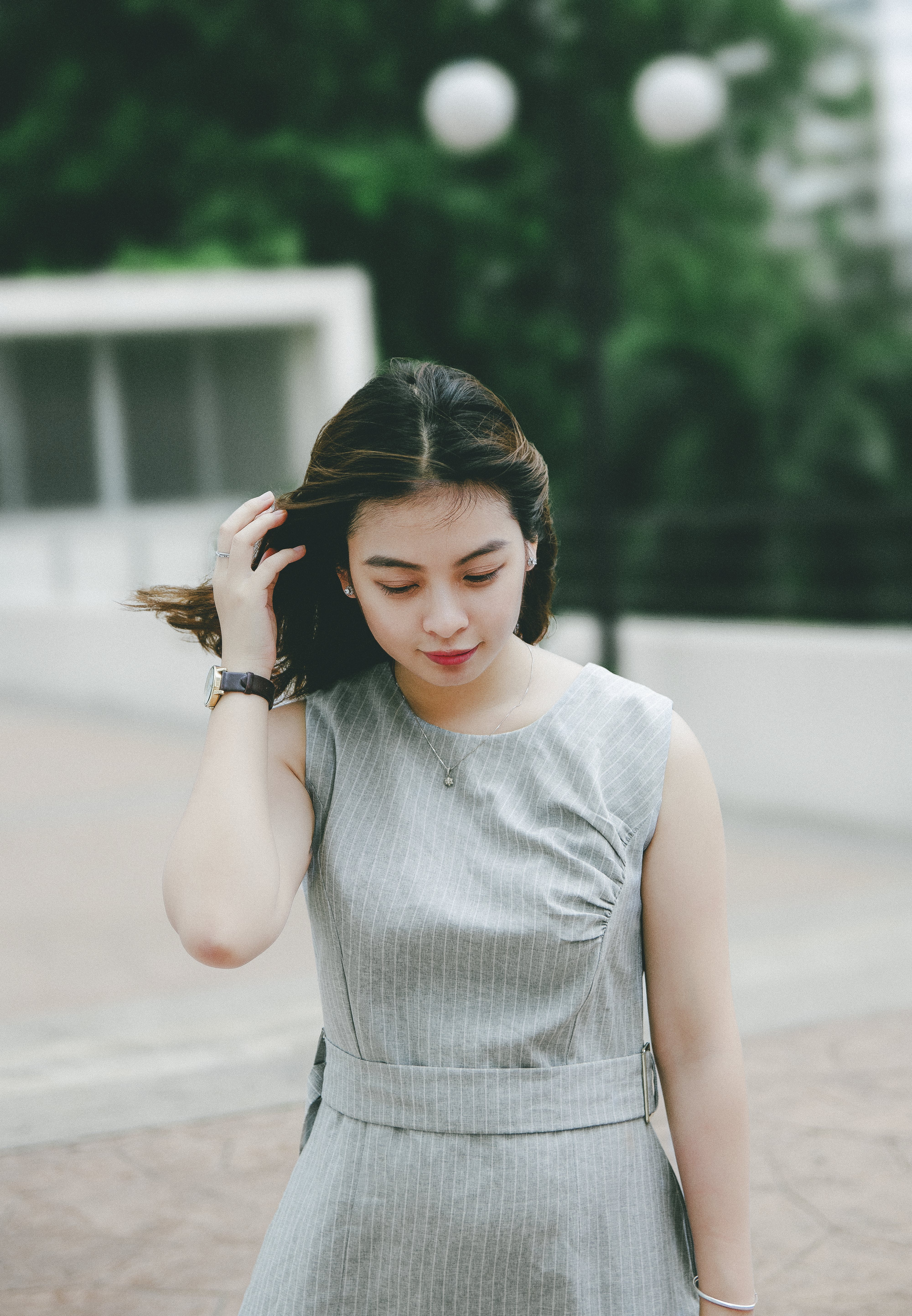 Selective Focus Photography of Woman Wearing Gray Striped Sleeveless Dress Holding Hair