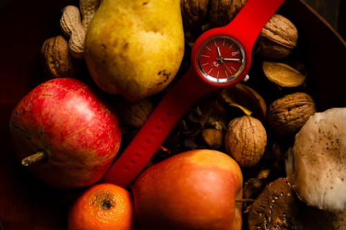 Stylish red wristwatch placed in basket with fresh fruits and vegetables