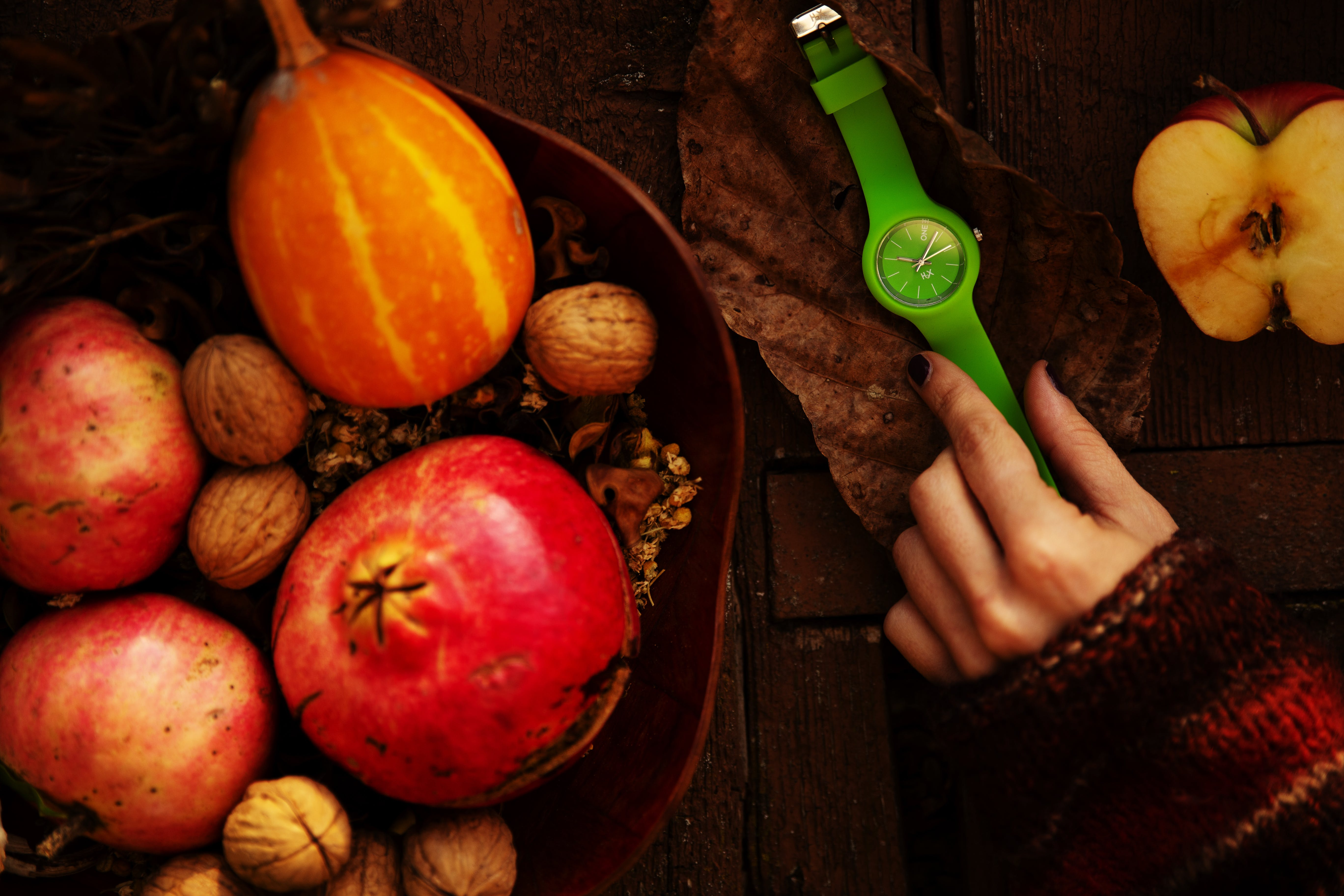 Person Touching Green Analog Watch Between Sliced Apple and Fruit Basket