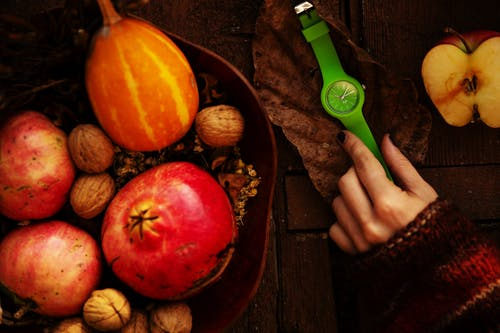 Crop woman with trendy wristwatch near basket of organic fruits and nuts