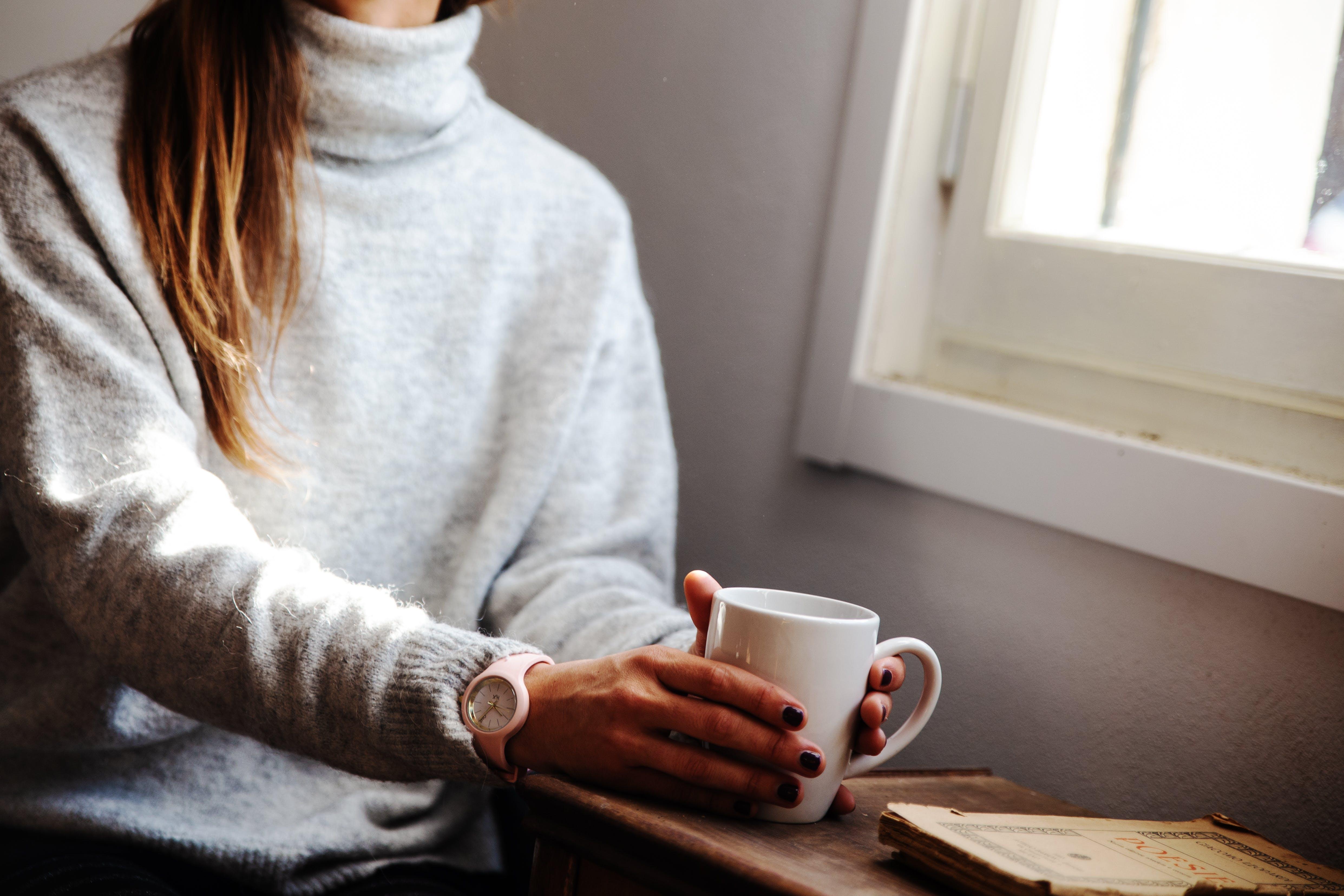 Woman Holding Coffee Mug While Sitting Beside Window