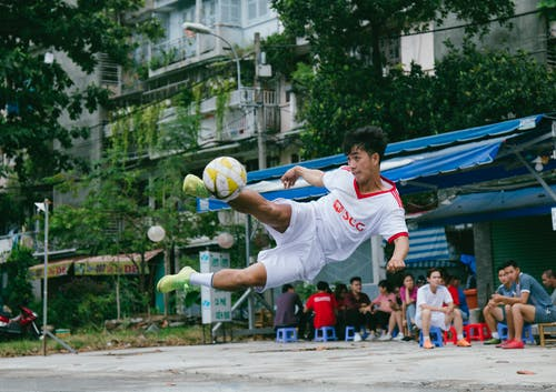 Soccer Player Kick the Ball Near People Sitting on Canopy Tent