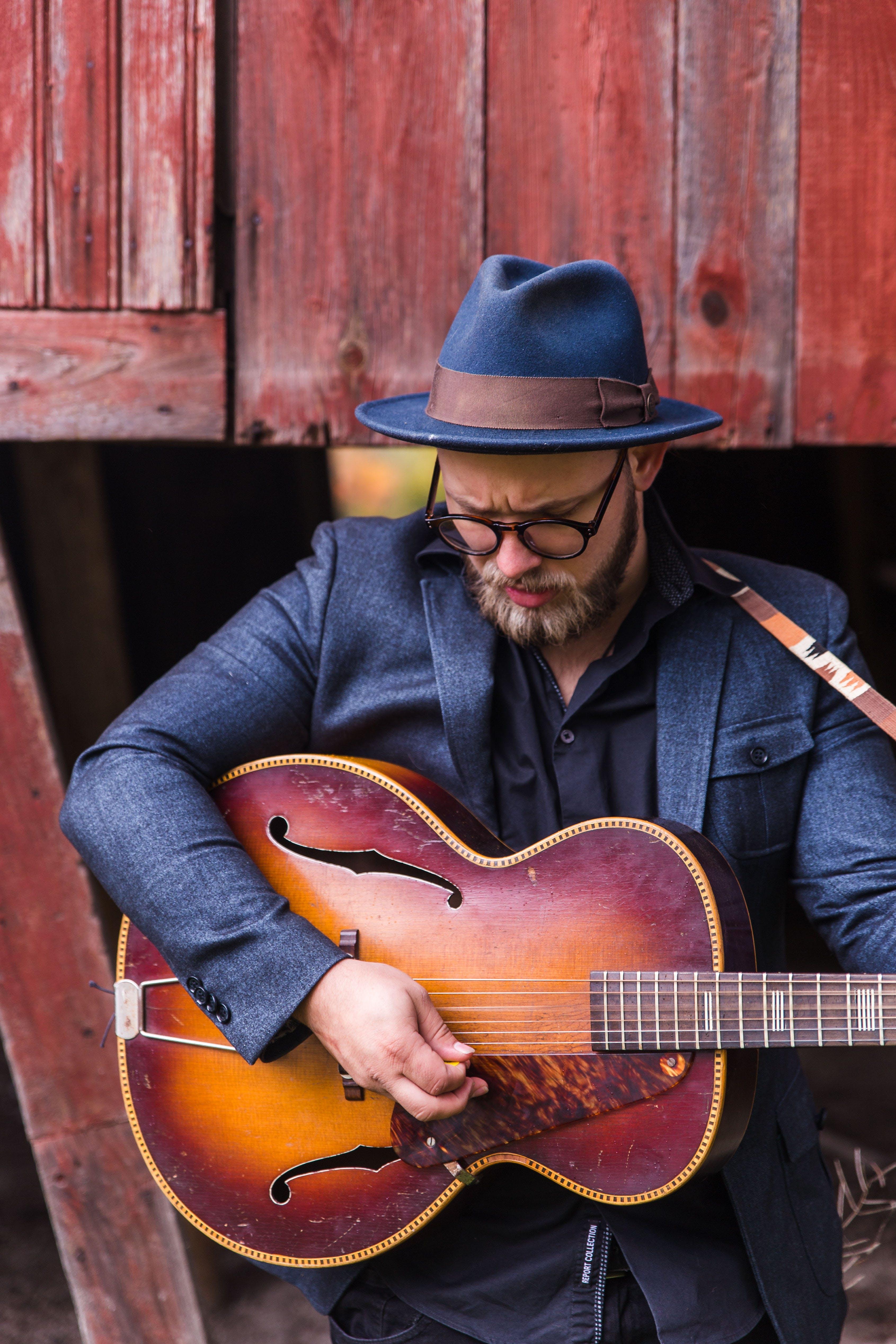Man Holding Jazz Guitar Standing Beside Brown Wooden Wall