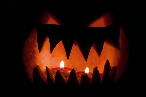 Бесплатное стоковое фото с апельсин, вырезанная тыква, горящая свеча, огонь