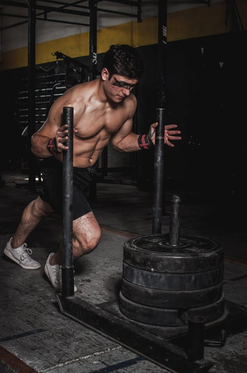 Man Pushing Steel Frame With Pile of Weight Plates