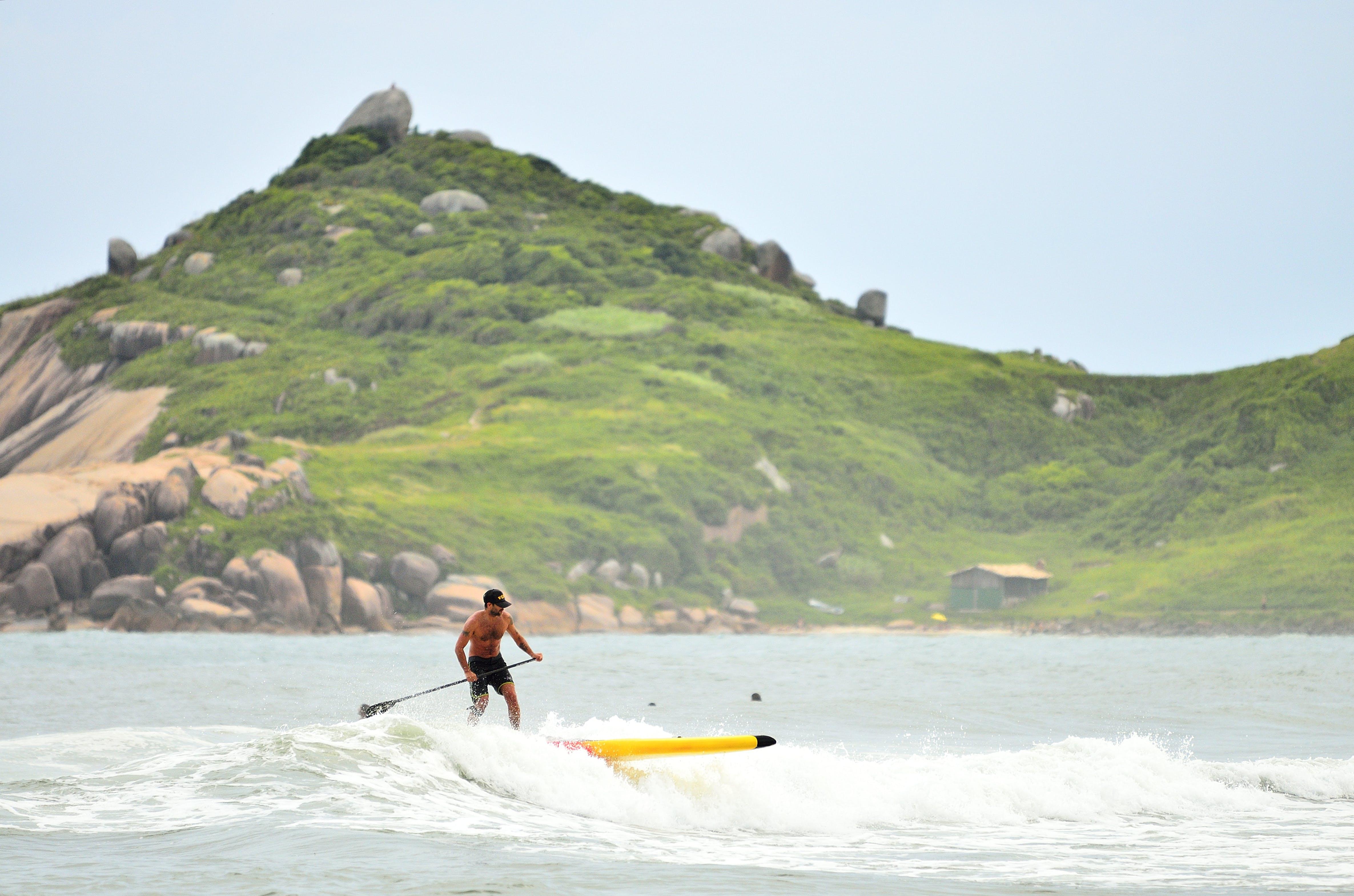 Man in Black Shorts Surfing Under Blue Sky during Daytime