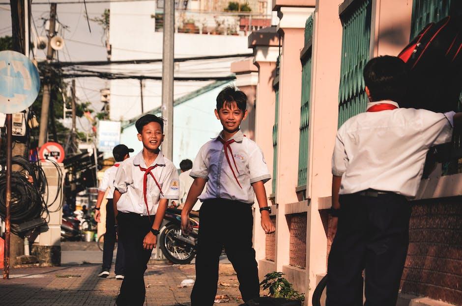 Three Boys Standing on Sidewalk