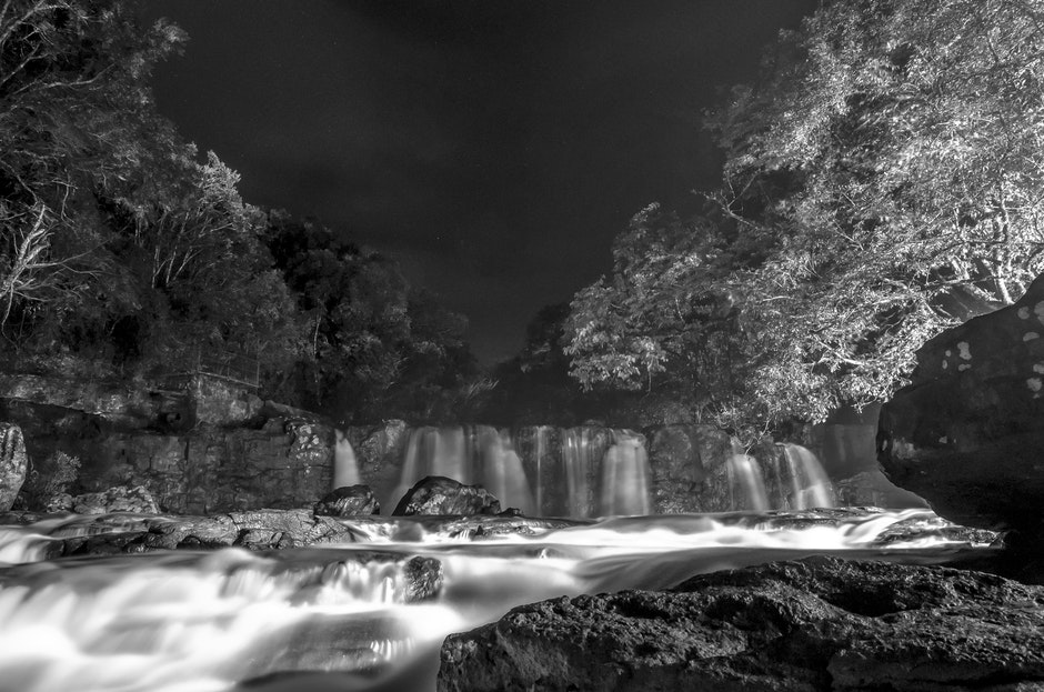 Greyscale Photo of Waterfall during Nighttime