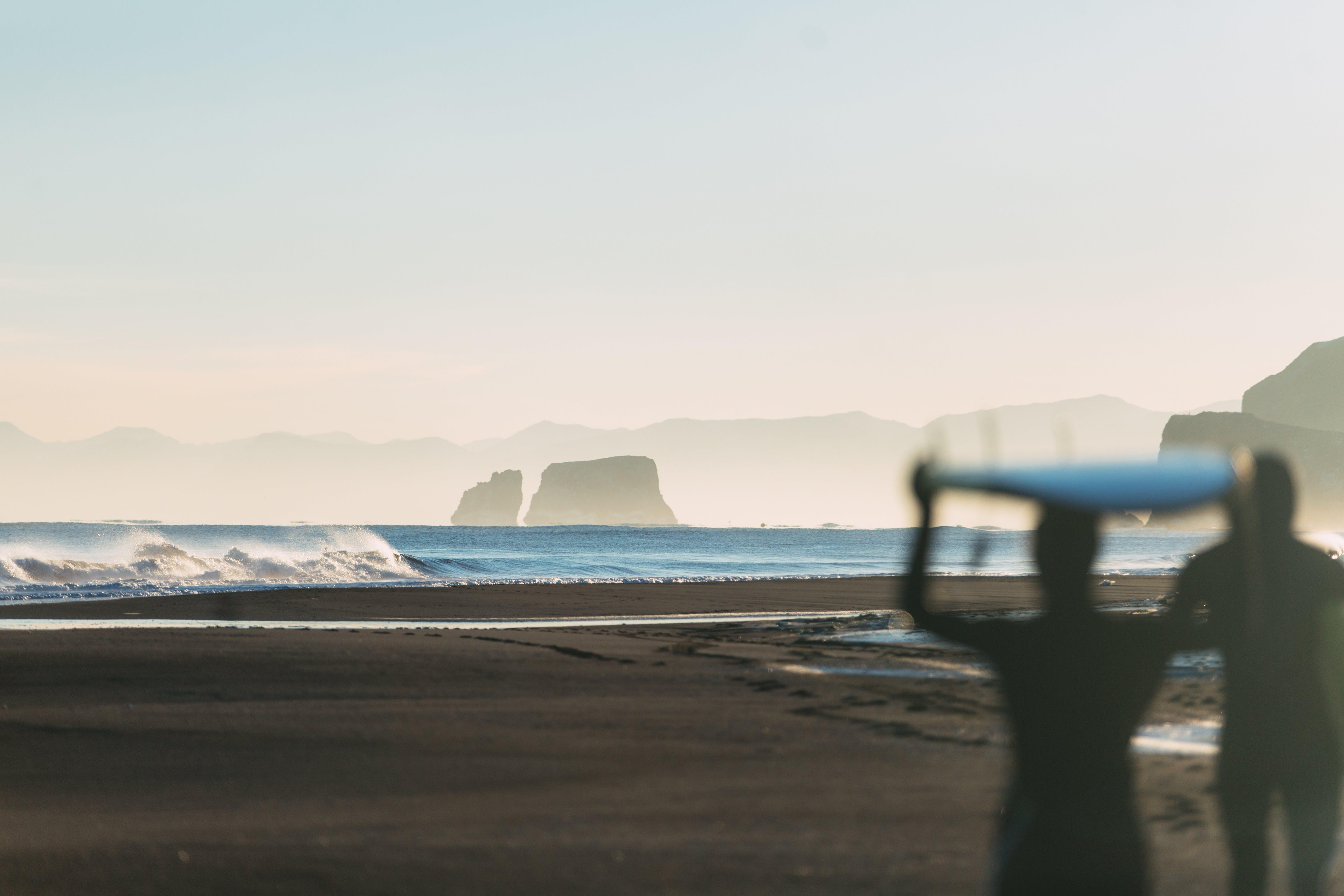 Silhouette of Person Holding Surfboard Near Seashore