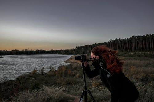 Woman in Black Coat Holding Dslr Camera With Stand Near Body of Water