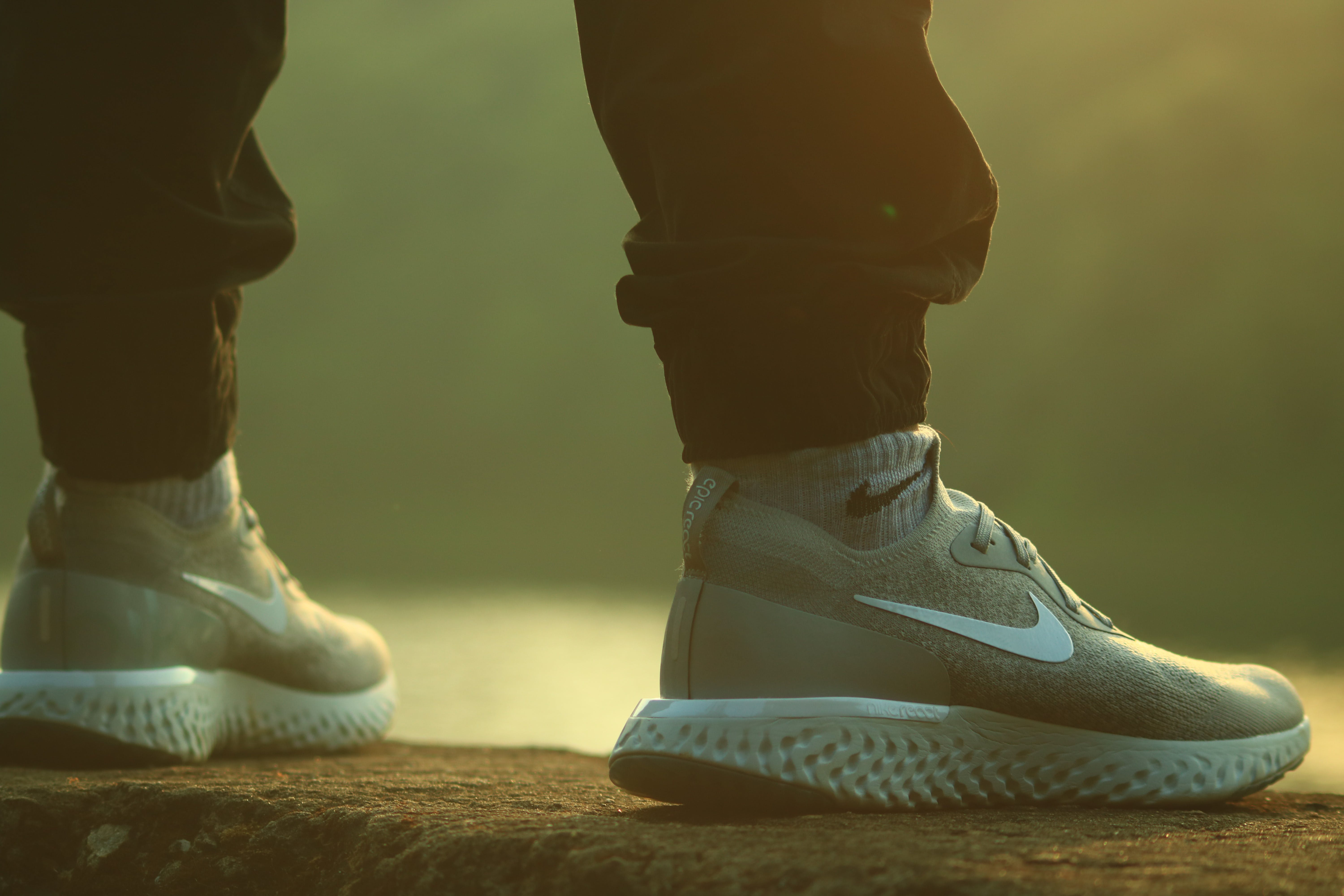 Standing Person Wearing Black Jogger Pants and Gray-and-white Nike React Running Shoes on Concrete Ground