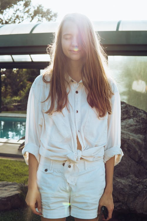 Woman Wearing White Button-up Long-sleeved Shirt and White Shorts Standing Near Swimming Pool