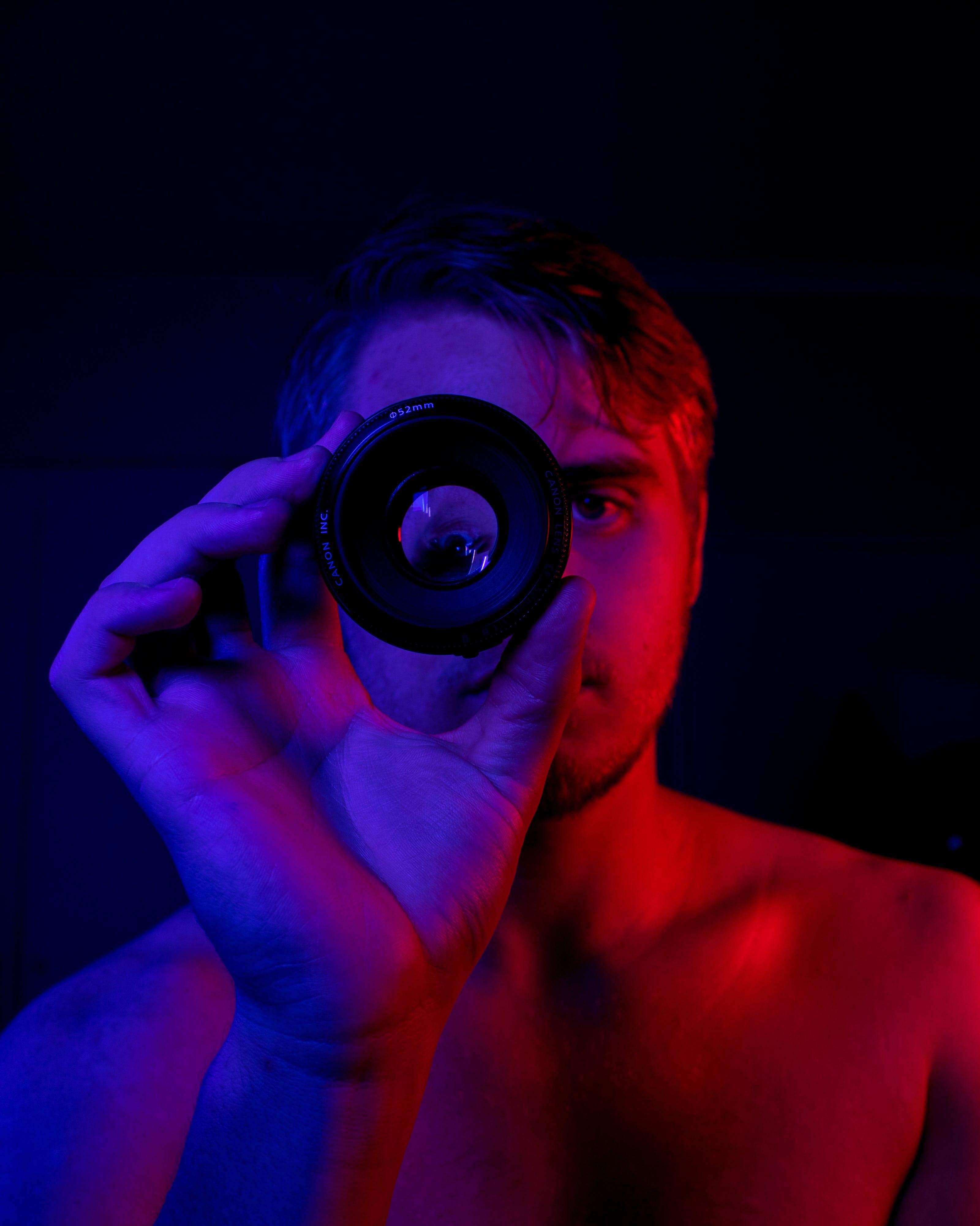 Topless Man Holding Round Black Mirror Device