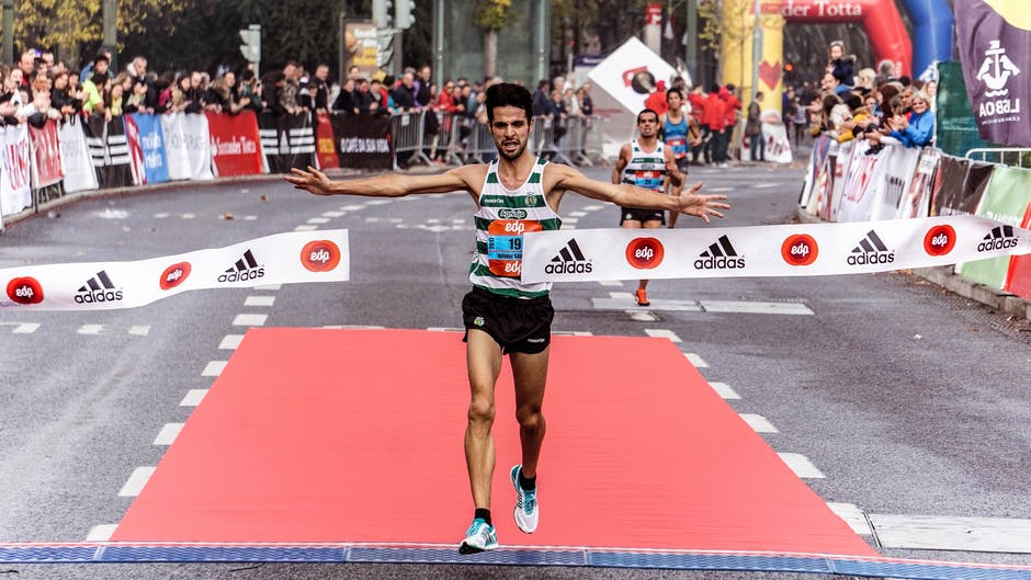 Man running through the finish line of a race.