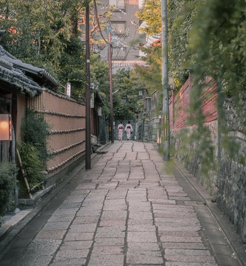 Two People Walking In A Alley