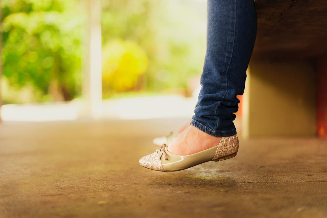 Person Wearing Beige Flats While Sitting on Bench