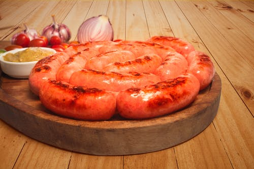 Sausages on Top of Brown Wooden Board
