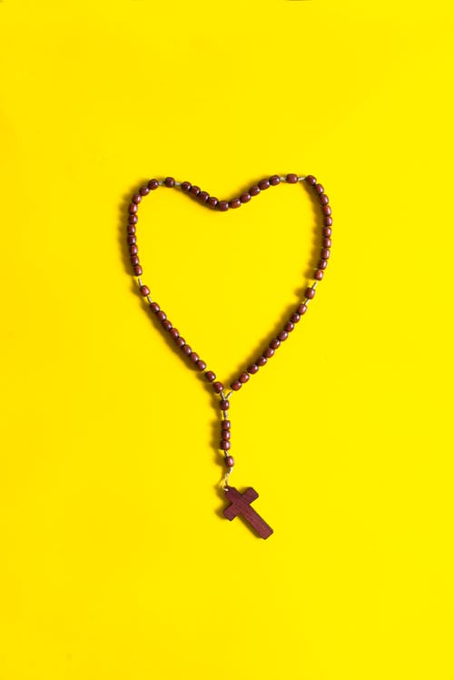 Brown Rosary on Yellow Surface