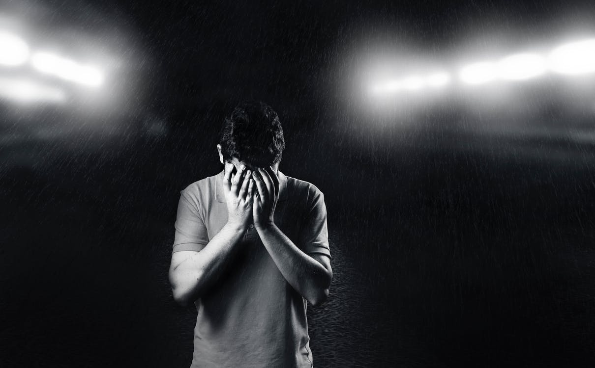 Monochrome Photo of Man Covering His Face