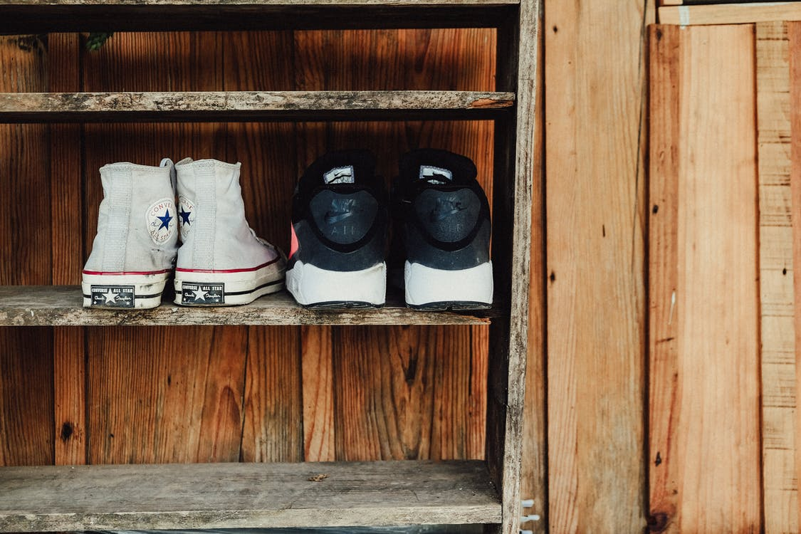 Two Pairs of Gray and Black Sneakers on Rack