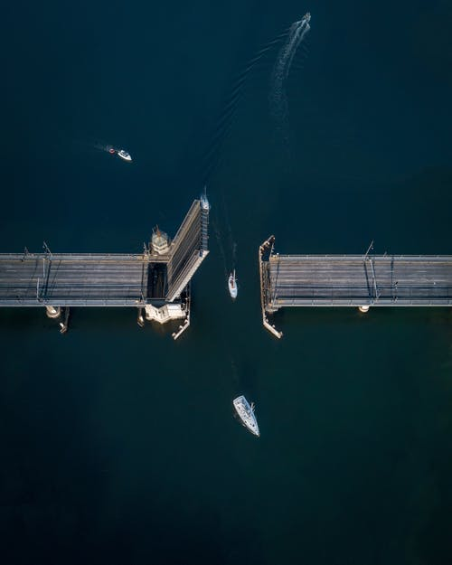 High-angle Photography of White Sailboat Crossing Bridge