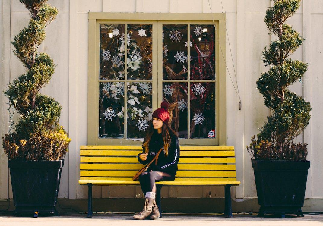 Woman Sitting on Yellow Bench