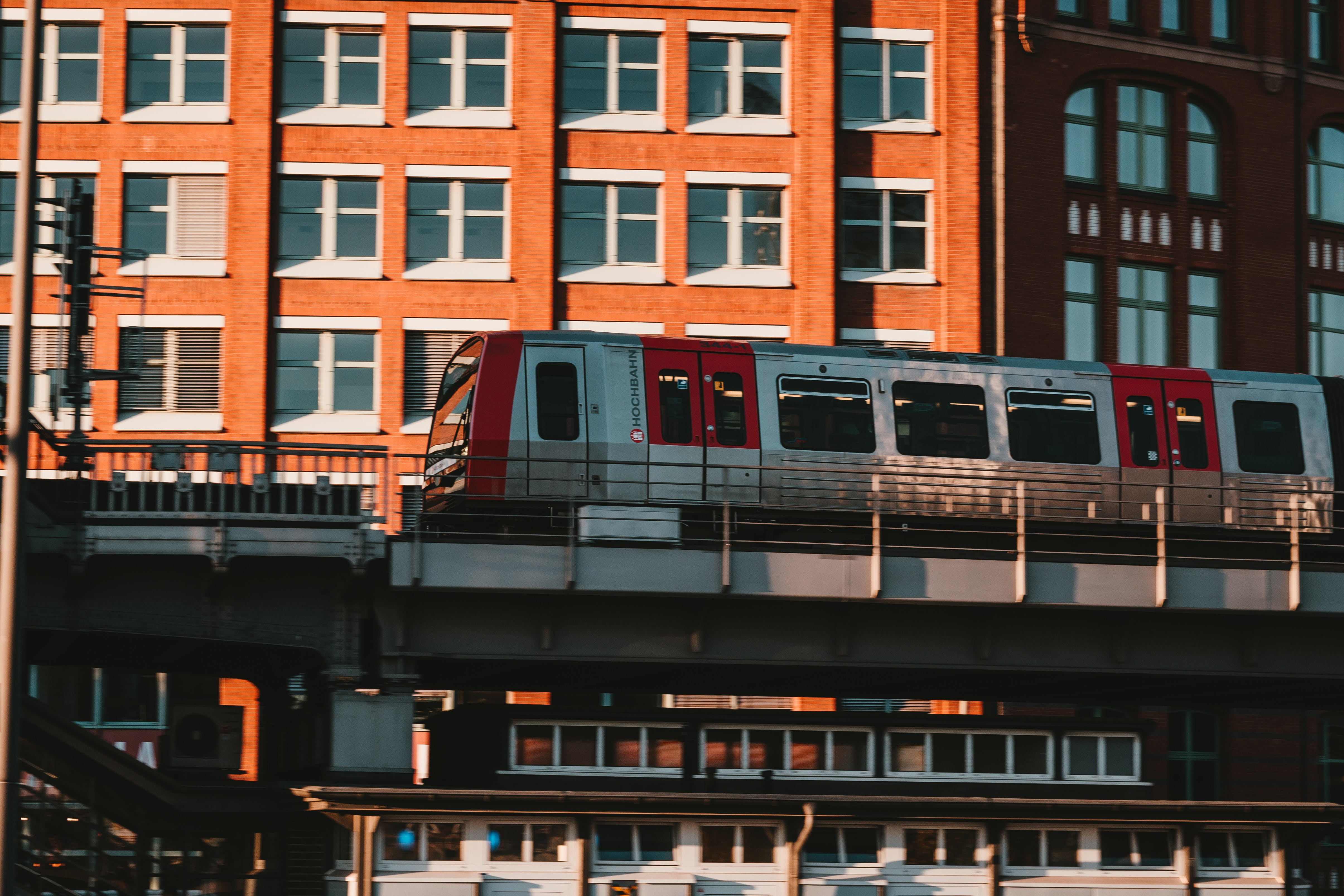 White and Red Train Near Brown Concrete Building