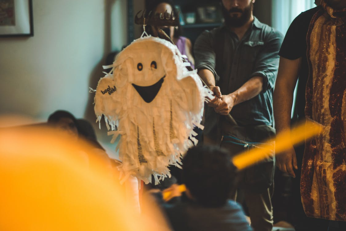 Person Holding Stick in Front of White Ghost Pinata