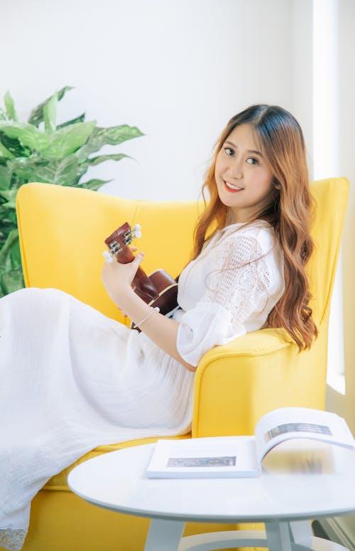 Woman Playing Ukulele on Armchair