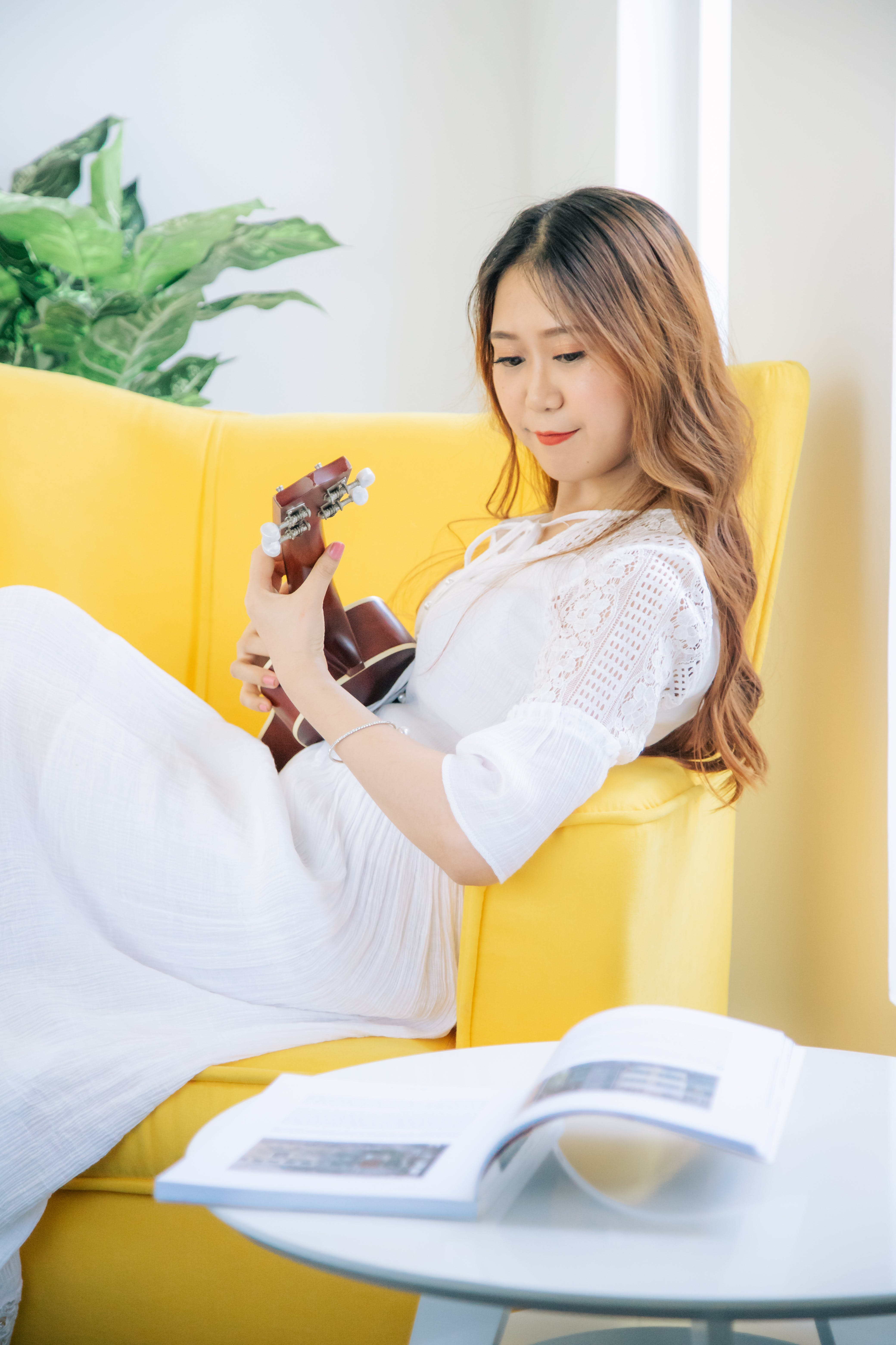 Woman Sitting on Sofa While Playing Ukulele