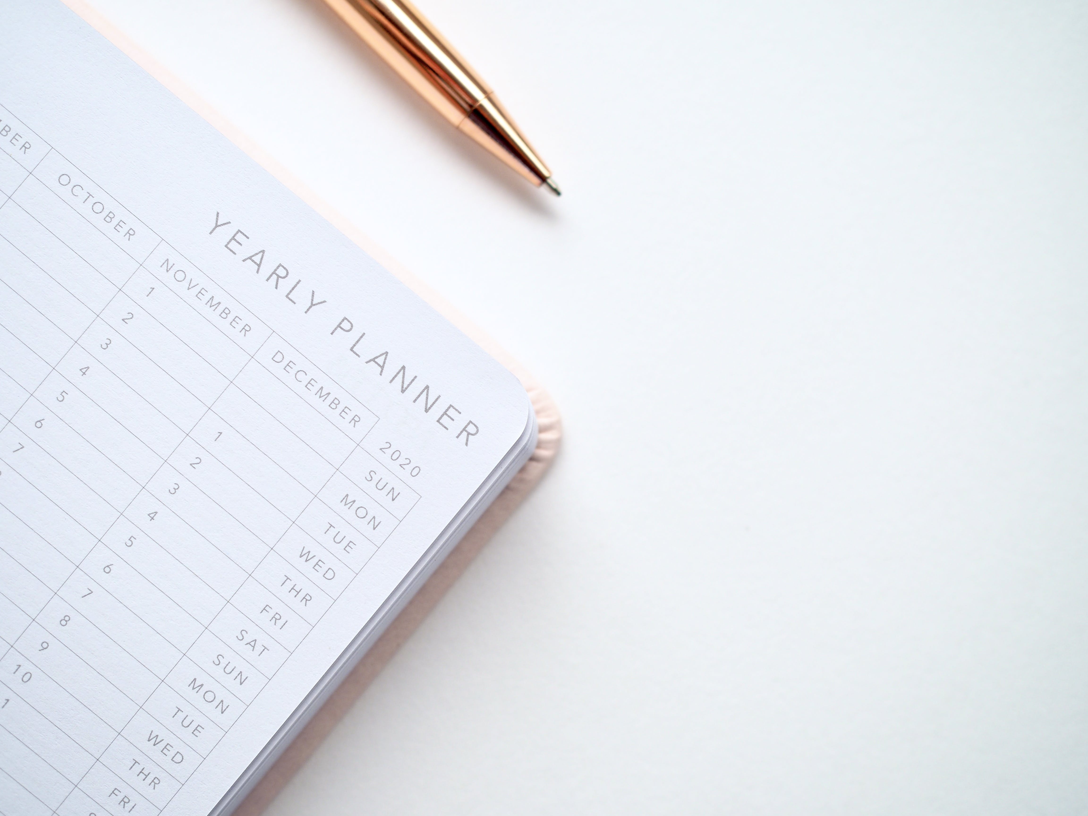 Close-Up Photo of Yearly Planner Beside a Pen