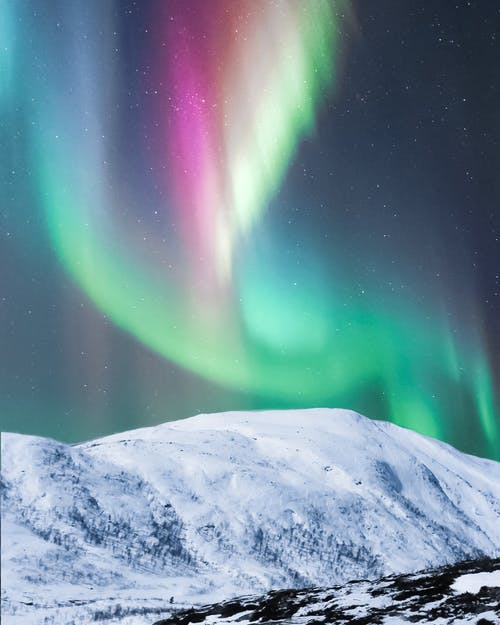 Colorful polar lights over snowy mountain