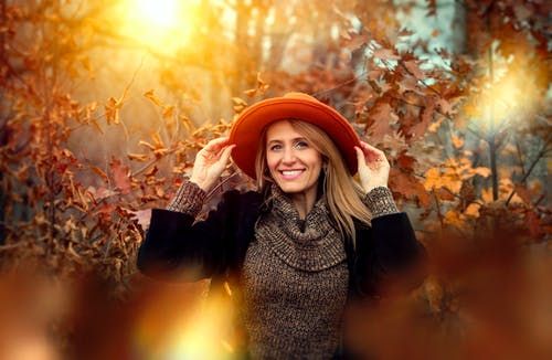 Smiling Woman Holding Orange Sun Hat