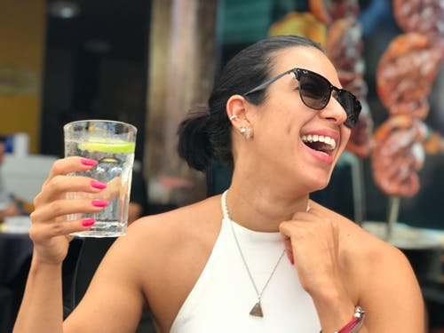 Photo of a Woman Holding a Glass of Water