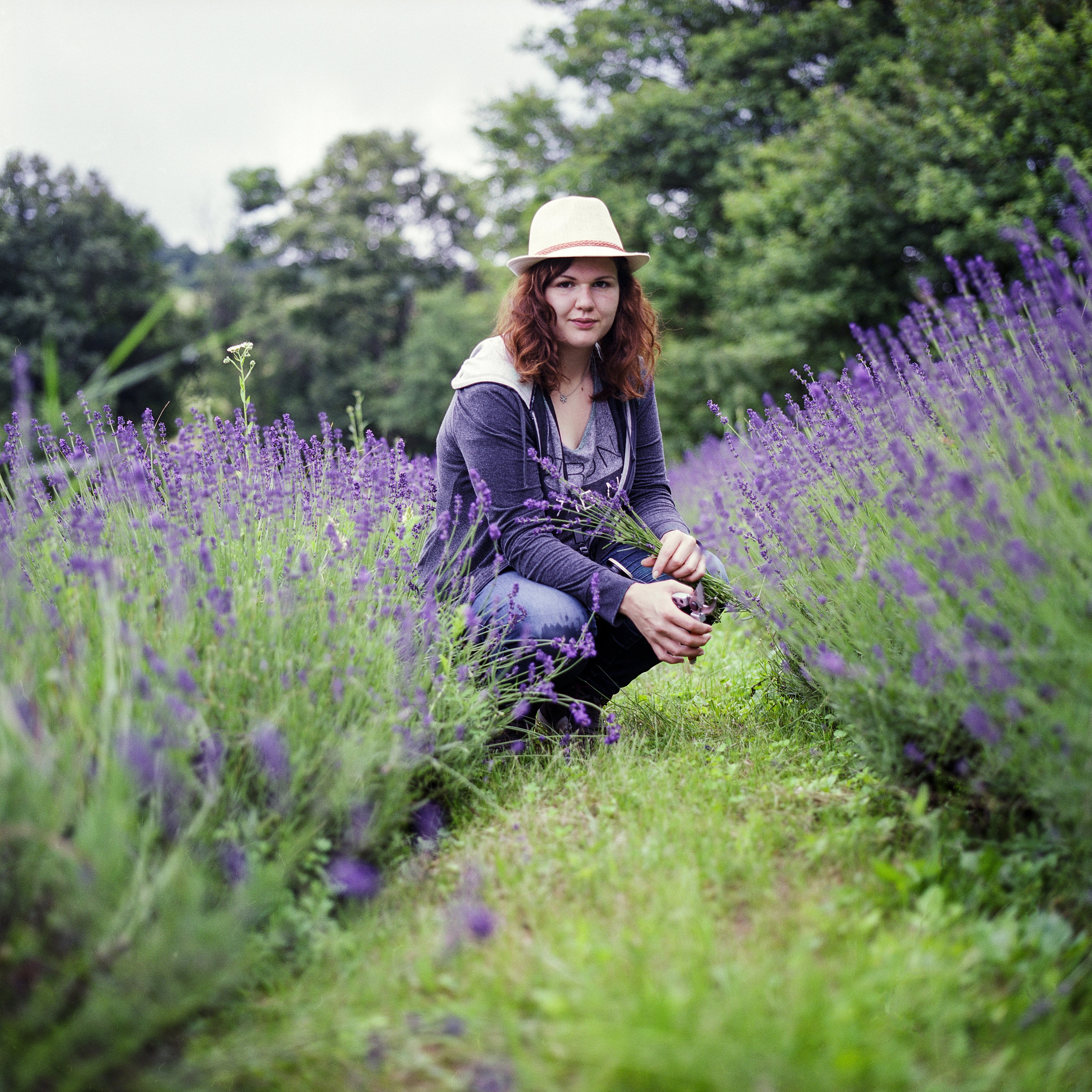 Woman Wearing Purple Jacket in Brown Hat during Day Time