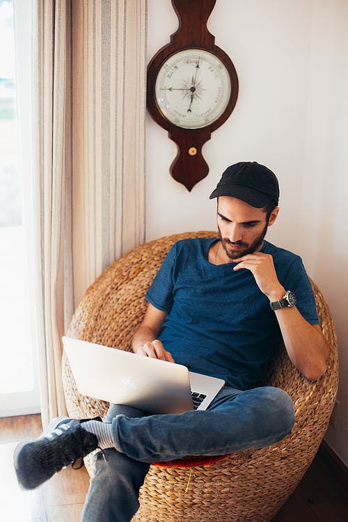 Man in Blue Top Sitting on Wicker Chair While Using Laptop