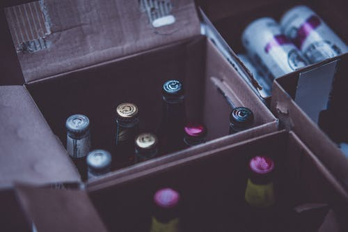 Glass Bottles on Boxes Close-up Photography